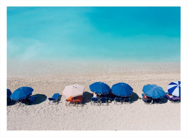 Blåa parasoll på rad vid tropiskt hav på en sandstrand