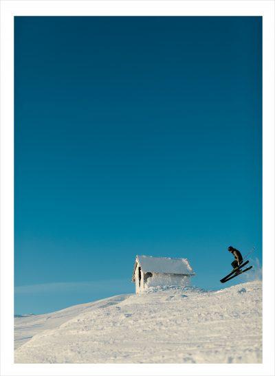 En skidåkare på fjället under blå himmel