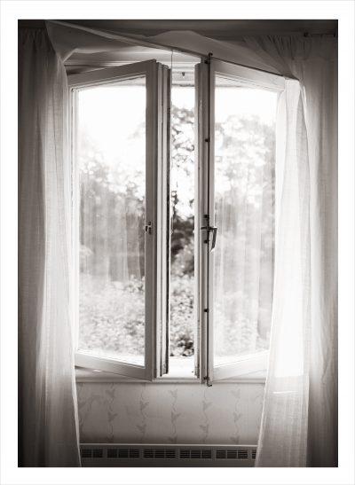 Halvöppet fönster med gardiner och sol utanför