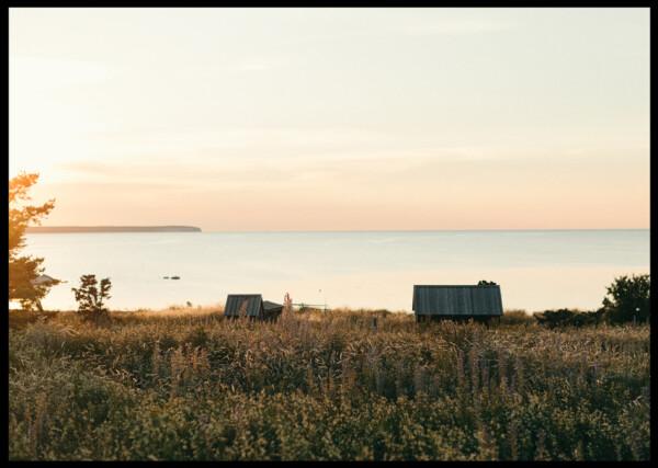 Inramad poster av stuga vid havet bakom ett gräsfält