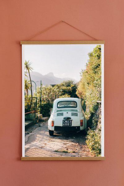 Fiatbil på poster med hängande ram på röd vägg