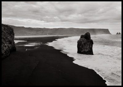 Svart strand vid havet inramat i svart