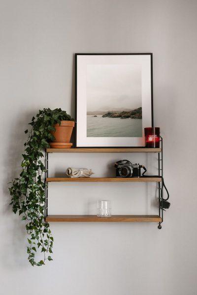 Stringhylla med fotokonst och poster