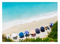 Solig dag på stranden med massor av parasoll i Grekland