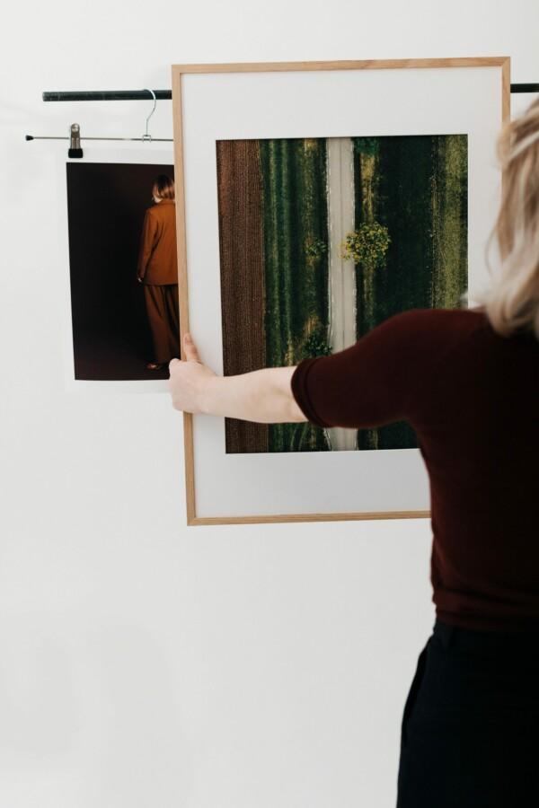 En kvinna håller upp en inramad poster av en väg ovanifrån