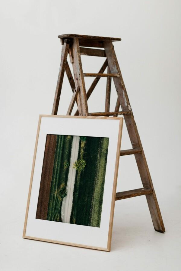 En inramad poster av väg ovanifrån, vilandes på en gammal stege i en studio