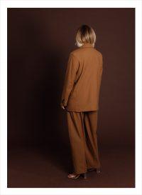 Människa klädd i brunt baikfrån som ser som en skyltdocka