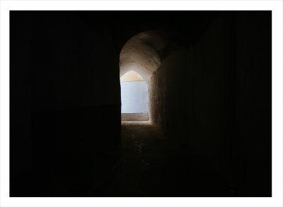 Ett mörkt rum med litet fönster som släpper in lite solljus