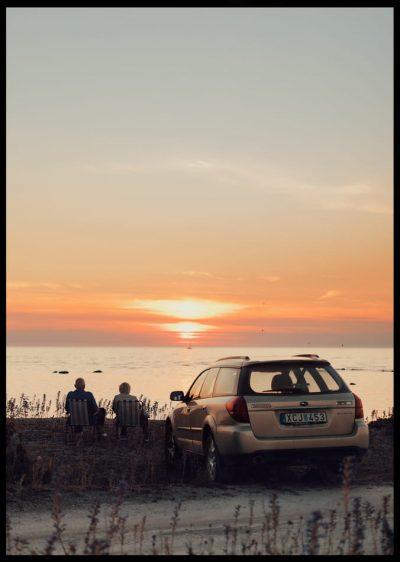 Inramad med svart ram en poster av ett par som tittar på solnedgången