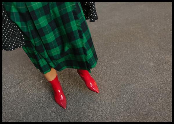 Inramad med svart ram en poster av en grönrutig klänning med röda skor