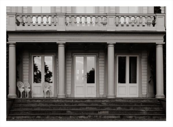 Mirrors - En svartvit veranda med mycket fönster och en trapp