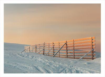Ett frostigt staket på fjället med solljus i solnedgång