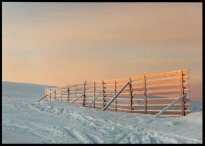 Inramad med svart ram en poster av ett frostigt staket upp på ett fjäll