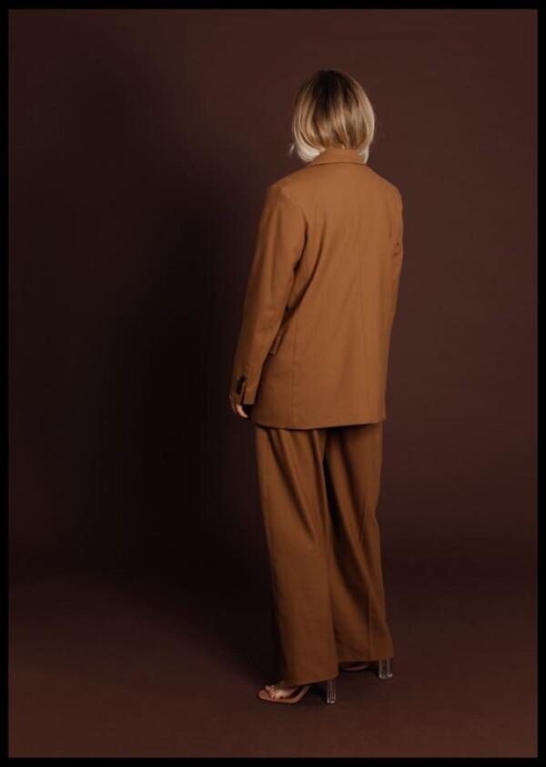 Inramad med svart ram en poster av en människa bakifrån klädd i brunt