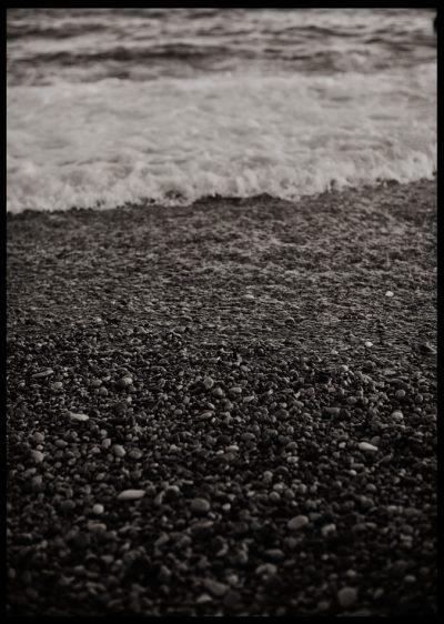 Inramad med svart ram en poster av svartvitt strand och skum från våg