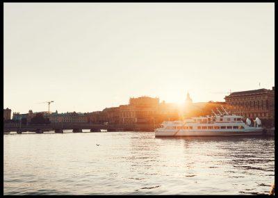 Inramad med svart ram en poster av mälaren i solnegång och en båt