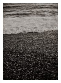Stenstrand i svartvitt med skum från vågor