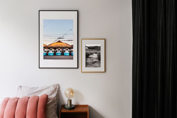 Fotokonst poster ovanför säng och nattduksbord