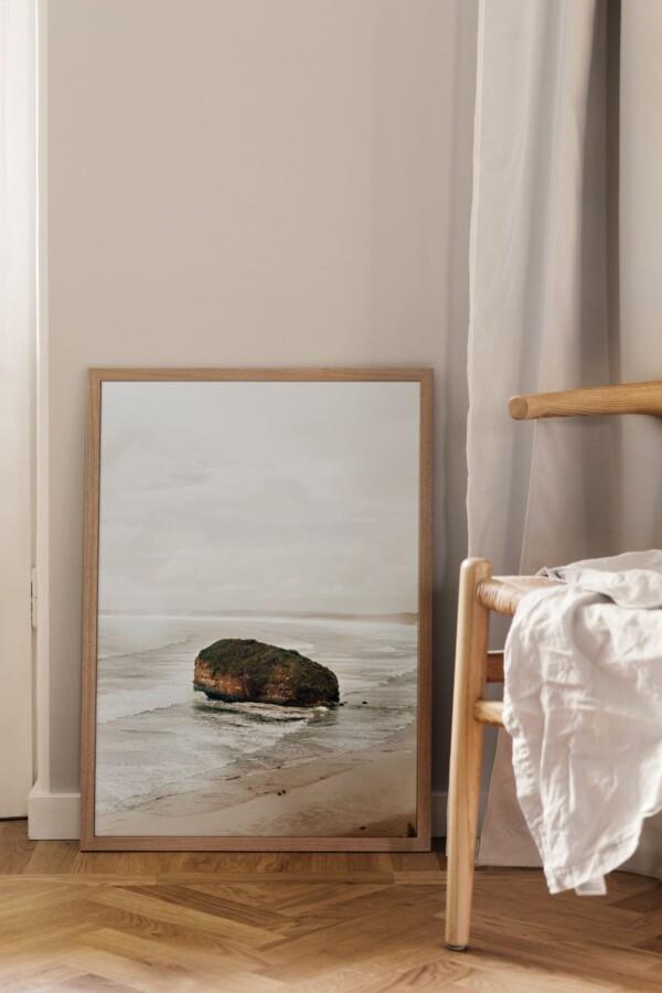 Poster och fotokonst på golvet vid stol