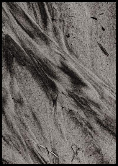 Inramad med svart ram en poster av närbild av strand