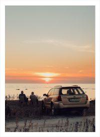 Par vid bil tittar på solnedgången på Gotland